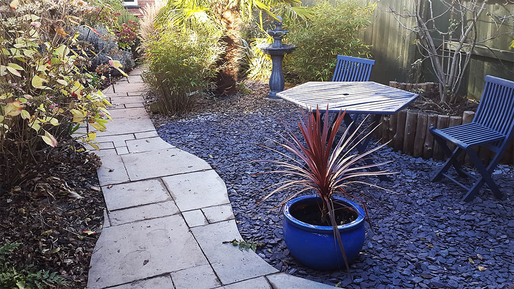 Gravelled seating area in verdant garden